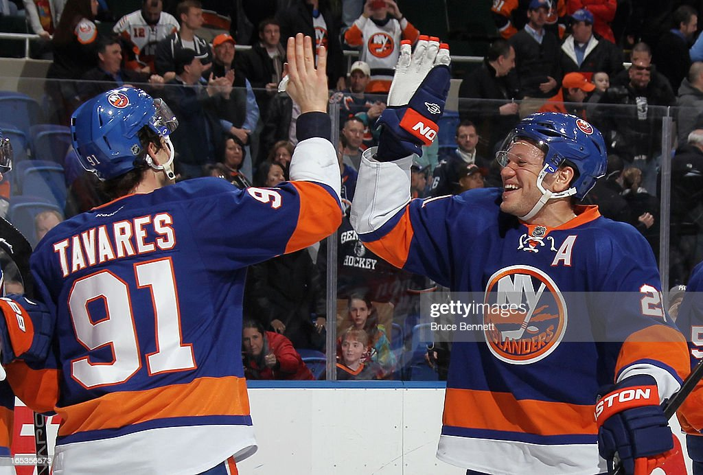 John Tavares #91 and Kyle Okposo #21 of the New York Islanders celebrate their win against the Winnipeg Jets at the Nassau Veterans Memorial Coliseum on April 2, 2013 in Uniondale, New York. The Islanders defeated the Jets 5-2.