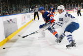 John Tavares of the New York Islanders and Francois Beauchemin of the Toronto Maple Leafs battle for the puck on March 14 2010 at Nassau Coliseum in...