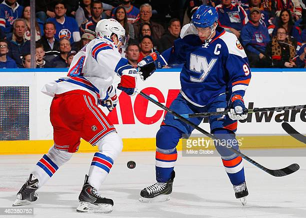 John Tavares of the New York Islanders and Matt Hunwick of the New York Rangers battle for the puck at Nassau Veterans Memorial Coliseum on January...