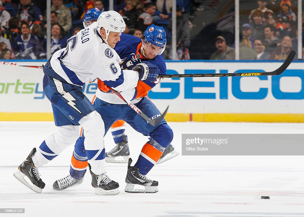 John Tavares #91 of the New York Islanders and Sami Salo #6 of the Tampa Bay Lightning battle in pursuit of the puck at Nassau Veterans Memorial Coliseum on January 21, 2013 in Uniondale, New York. The Islanders defeated the Lightning 4-3.