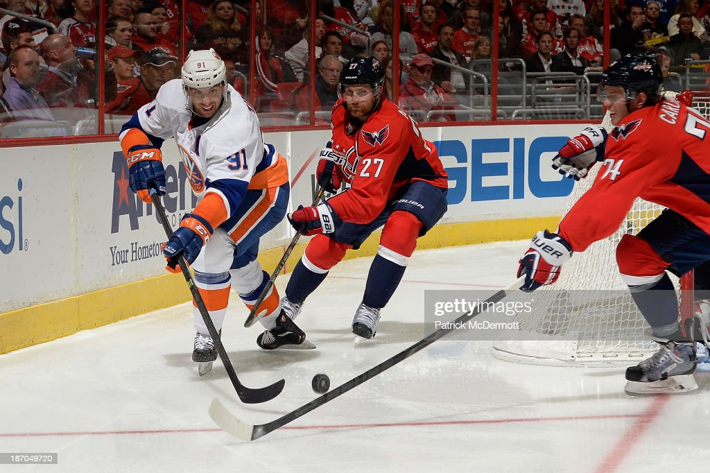 <a gi-track='captionPersonalityLinkClicked' href=/galleries/search?phrase=John+Tavares&family=editorial&specificpeople=601791 ng-click='$event.stopPropagation()'>John Tavares</a> #91 of the New York Islanders battles for the puck against <a gi-track='captionPersonalityLinkClicked' href=/galleries/search?phrase=Karl+Alzner&family=editorial&specificpeople=3938829 ng-click='$event.stopPropagation()'>Karl Alzner</a> #27 and John Carlson #74 of the Washington Capitals in the third period of an NHL game at Verizon Center on November 5, 2013 in Washington, DC.