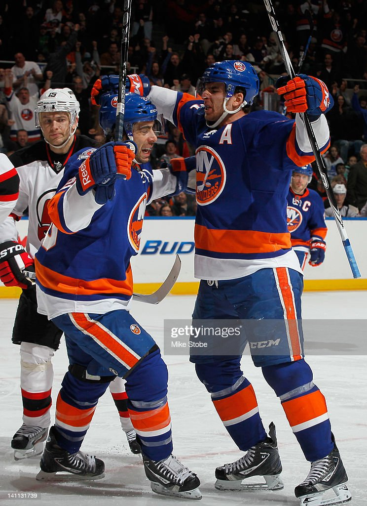 <a gi-track='captionPersonalityLinkClicked' href=/galleries/search?phrase=John+Tavares&family=editorial&specificpeople=601791 ng-click='$event.stopPropagation()'>John Tavares</a> #91 of the New York Islanders celebrates his third period goal with teammate <a gi-track='captionPersonalityLinkClicked' href=/galleries/search?phrase=Matt+Moulson&family=editorial&specificpeople=3365493 ng-click='$event.stopPropagation()'>Matt Moulson</a> #26 in a game against the New Jersey Devils at Nassau Veterans Memorial Coliseum on March 10, 2012 in Uniondale, New York.