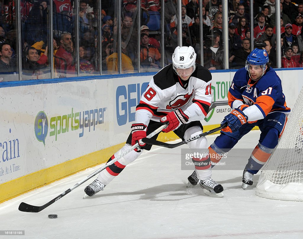John Tavares #91 of the New York Islanders challenges Steve Bernier #18 of the New Jersey Devils for the puck during the game on February 16, 2013 at Nassau Veterans Memorial Coliseum in Uniondale, New York.