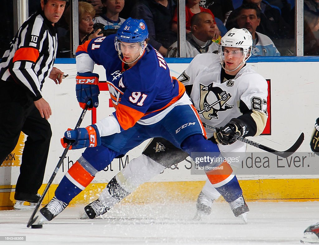 John Tavares #91 of the New York Islanders controls the puck in front of Sidney Crosby #87 of the Pittsburgh Penguins in an NHL hockey game at Nassau Veterans Memorial Coliseum on March 22, 2013 in Uniondale, New York.