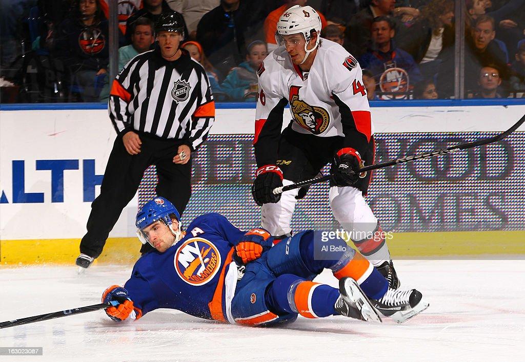 John Tavares #91 of the New York Islanders falls as Patrick Wiercioch #46 of the Ottawa Senators follows during their game at Nassau Veterans Memorial Coliseum on March 3, 2013 in Uniondale, New York.