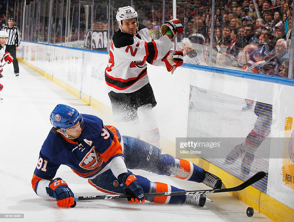 John Tavares #91 of the New York Islanders falls to the ice while pursuing the puck in front of David Clarkson #23 of the New Jersey Devils at Nassau Veterans Memorial Coliseum on February 16, 2013 in Uniondale, New York.