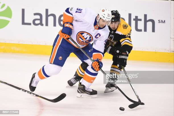 John Tavares of the New York Islanders fights for the puck against Brad Marchand of the Boston Bruins at the TD Garden on December 9 2017 in Boston...