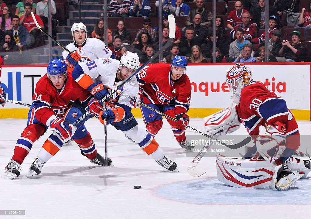 <a gi-track='captionPersonalityLinkClicked' href=/galleries/search?phrase=John+Tavares&family=editorial&specificpeople=601791 ng-click='$event.stopPropagation()'>John Tavares</a> #91 of the New York Islanders fights his way past defenseman Alexei Emelin #74 of the Montreal Canadiens as he tries to put the puck past goalie <a gi-track='captionPersonalityLinkClicked' href=/galleries/search?phrase=Peter+Budaj&family=editorial&specificpeople=228123 ng-click='$event.stopPropagation()'>Peter Budaj</a> #30 during the NHL game on March 17, 2012 at the Bell Centre in Montreal, Quebec, Canada.