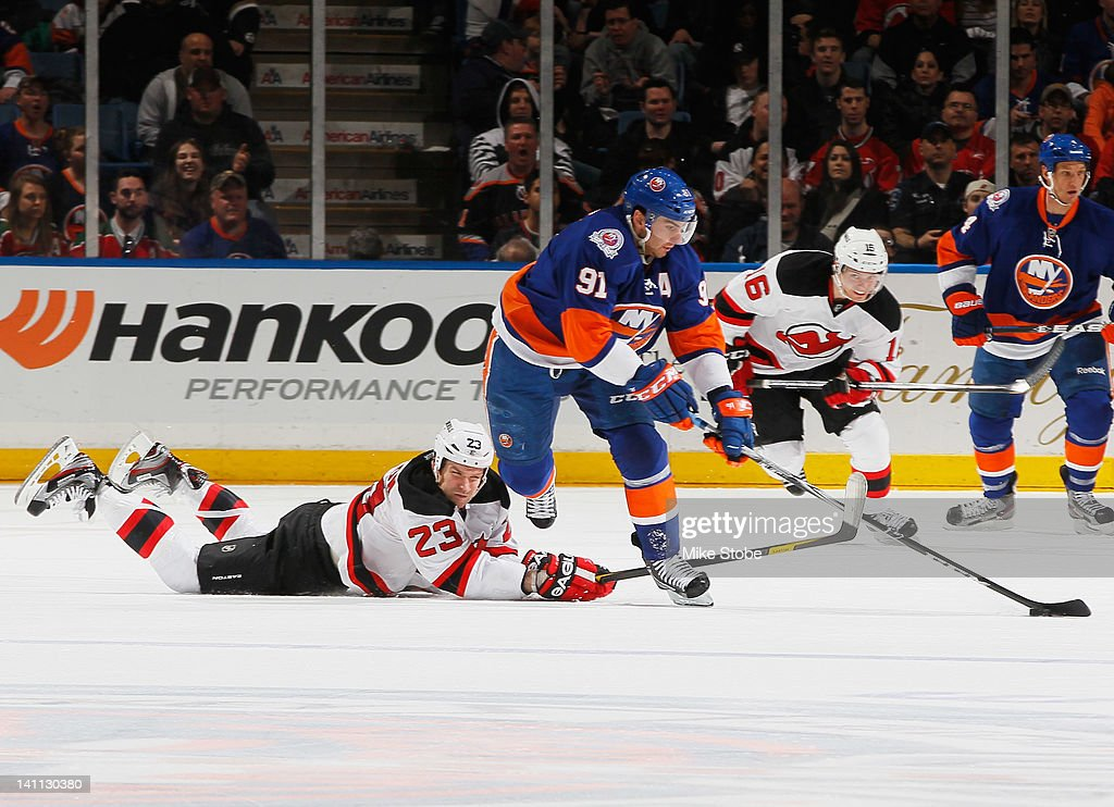 <a gi-track='captionPersonalityLinkClicked' href=/galleries/search?phrase=John+Tavares&family=editorial&specificpeople=601791 ng-click='$event.stopPropagation()'>John Tavares</a> #91 of the New York Islanders gains control of the puck as David Clarkson #23 of the New Jersey Devils falls to the ice at Nassau Veterans Memorial Coliseum on March 10, 2012 in Uniondale, New York.