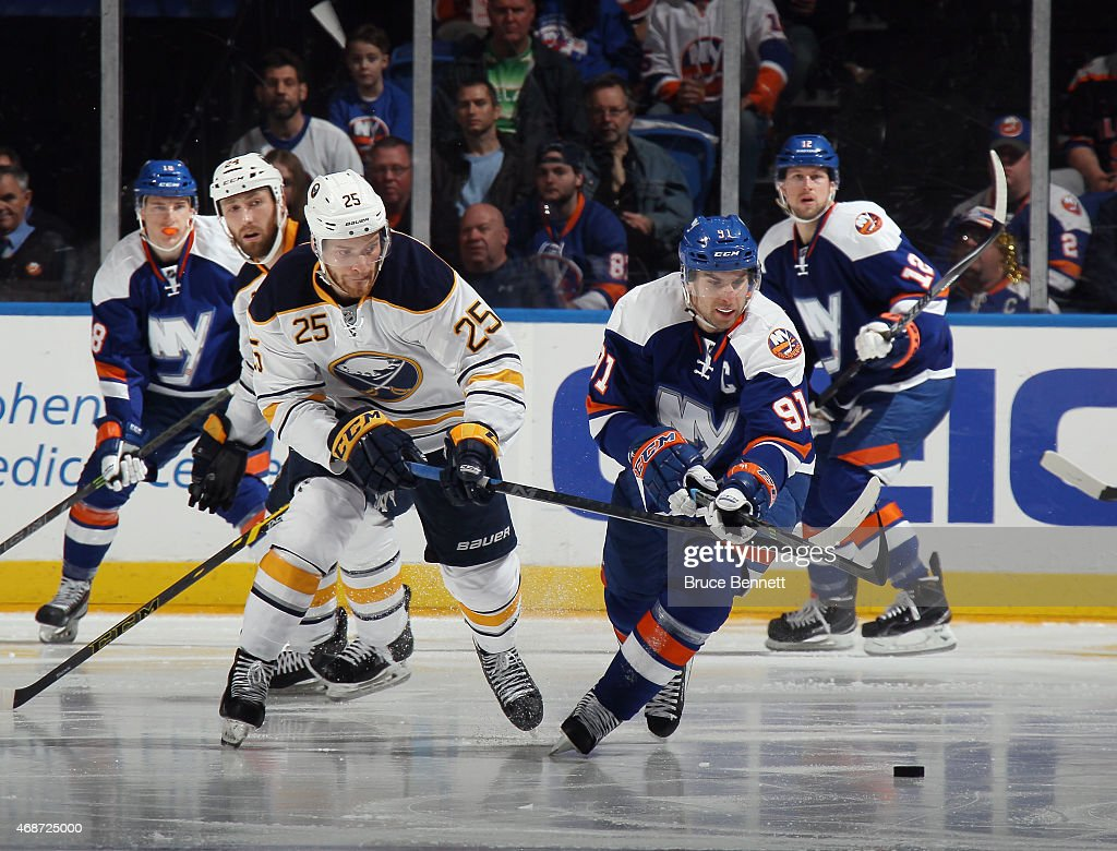 John Tavares #91 of the New York Islanders is checked by Mikhail Grigorenko #25 of the Buffalo Sabres at the Nassau Veterans Memorial Coliseum on April 4, 2015 in Uniondale, New York. The Islanders shut out the Sabres 3-0.