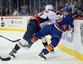 John Tavares of the New York Islanders is hit into the boards by Matt Niskanen of the Washington Capitals during the second period at the Barclays...
