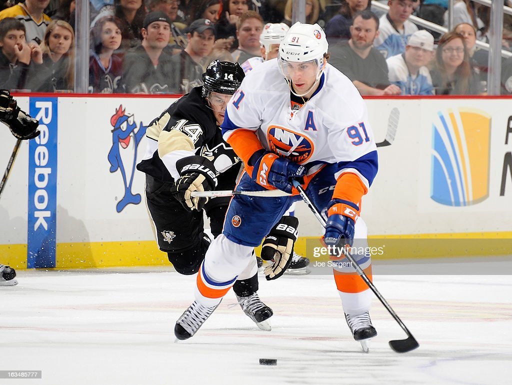 <a gi-track='captionPersonalityLinkClicked' href=/galleries/search?phrase=John+Tavares&family=editorial&specificpeople=601791 ng-click='$event.stopPropagation()'>John Tavares</a> #91 of the New York Islanders moves the puck up ice in front of <a gi-track='captionPersonalityLinkClicked' href=/galleries/search?phrase=Chris+Kunitz&family=editorial&specificpeople=604159 ng-click='$event.stopPropagation()'>Chris Kunitz</a> #14 of the Pittsburgh Penguins on March 10, 2013 at Consol Energy Center in Pittsburgh, Pennsylvania.