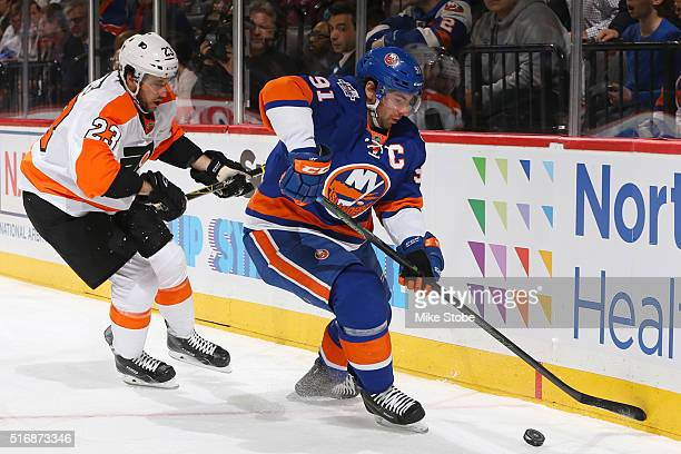 John Tavares of the New York Islanders plays the puck against Brandon Manning of the Philadelphia Flyers during the game at the Barclays Center on...