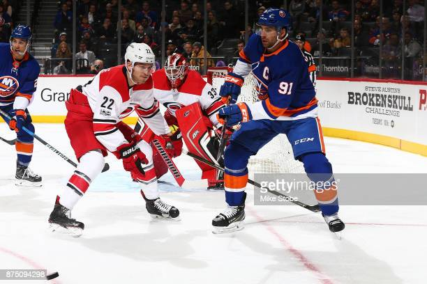 John Tavares of the New York Islanders plays the puck against Brett Pesce of the Carolina Hurricanes at Barclays Center on November 16 2017 in New...