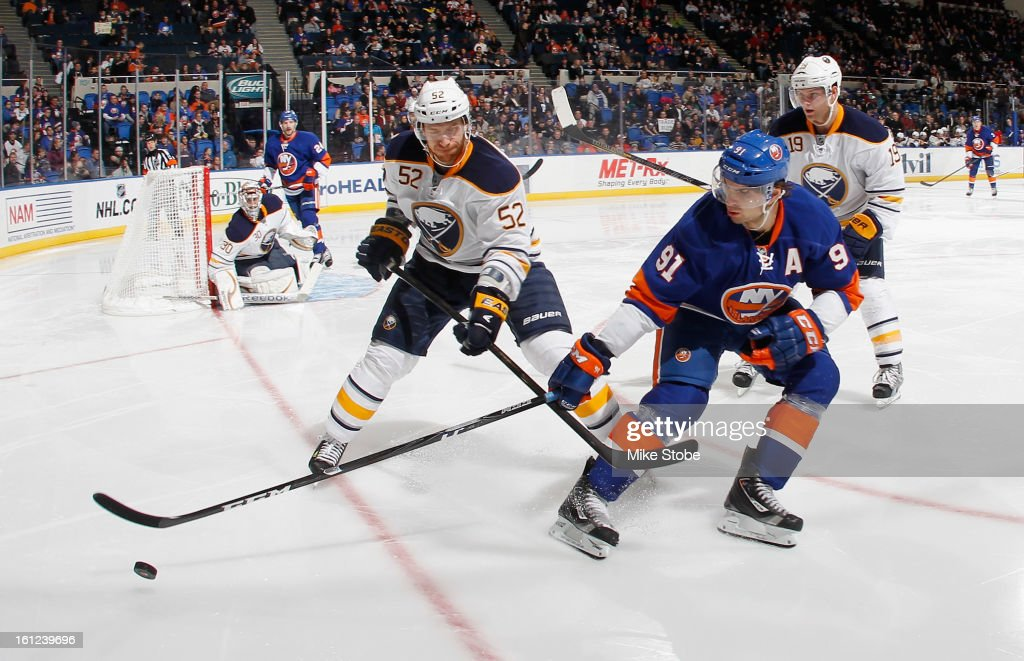 John Tavares #91 of the New York Islanders pursues the puck against Alexander Sulzer #52 of the Buffalo Sabres at Nassau Veterans Memorial Coliseum on Febuary 9, 2013 in Uniondale, New York. The Sabres defeated the Islanders 3-2.
