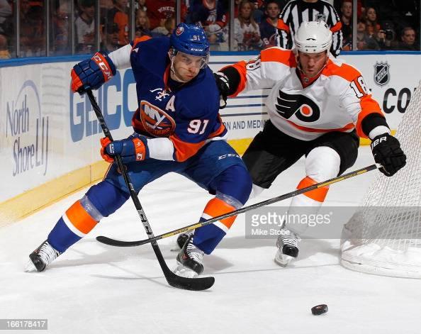 John Tavares of the New York Islanders skates against Adam Hall of the Philadelphia Flyers at Nassau Veterans Memorial Coliseum on April 9 2013 in...