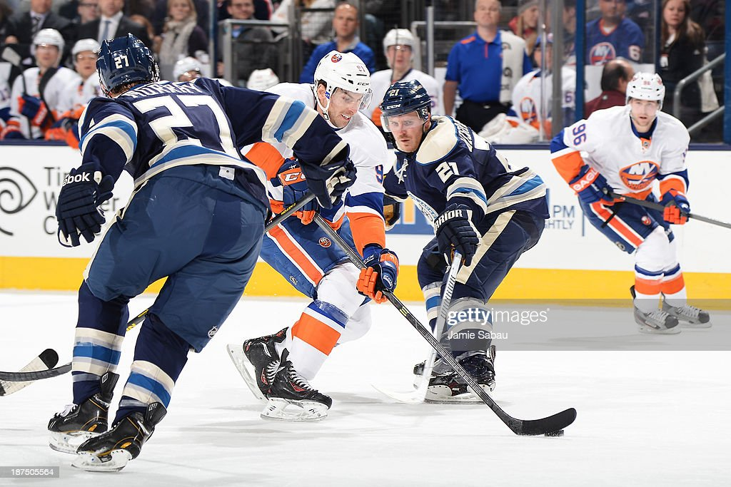 <a gi-track='captionPersonalityLinkClicked' href=/galleries/search?phrase=John+Tavares&family=editorial&specificpeople=601791 ng-click='$event.stopPropagation()'>John Tavares</a> #91 of the New York Islanders skates between the defense of Ryan Murray #27 and <a gi-track='captionPersonalityLinkClicked' href=/galleries/search?phrase=James+Wisniewski&family=editorial&specificpeople=688111 ng-click='$event.stopPropagation()'>James Wisniewski</a> #21 of the Columbus Blue Jackets during the second period on November 9, 2013 at Nationwide Arena in Columbus, Ohio.