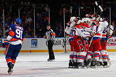 John Tavares of the New York Islanders skates off as the Washington Capitals celebrate the game winning goal in overtime by Nicklas Backstrom during...
