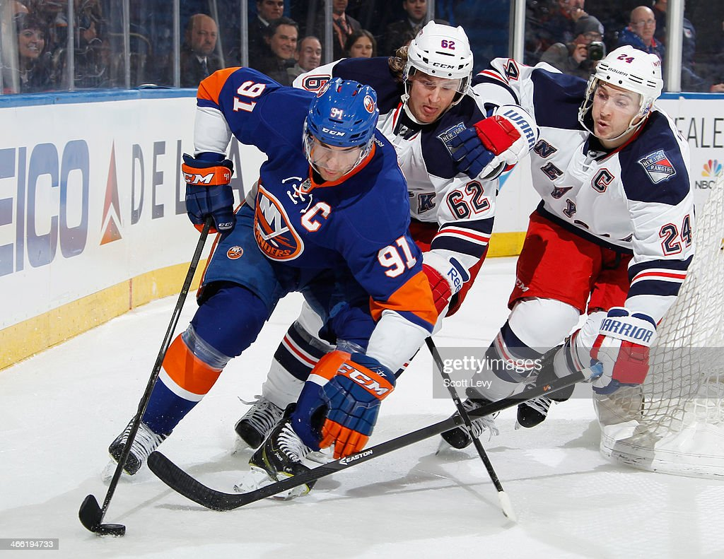 <a gi-track='captionPersonalityLinkClicked' href=/galleries/search?phrase=John+Tavares&family=editorial&specificpeople=601791 ng-click='$event.stopPropagation()'>John Tavares</a> #91 of the New York Islanders skates past <a gi-track='captionPersonalityLinkClicked' href=/galleries/search?phrase=Carl+Hagelin&family=editorial&specificpeople=4465394 ng-click='$event.stopPropagation()'>Carl Hagelin</a> #62 and <a gi-track='captionPersonalityLinkClicked' href=/galleries/search?phrase=Ryan+Callahan&family=editorial&specificpeople=809690 ng-click='$event.stopPropagation()'>Ryan Callahan</a> #24 of the New York Rangers with the puck at Madison Square Garden on January 31, 2014 in New York City.