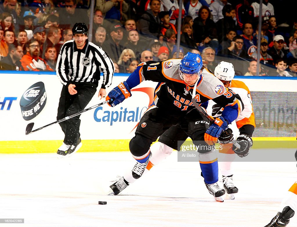 John Tavares #91 of the New York Islanders skates with the puck against the Philadelphia Flyers during their game at Nassau Veterans Memorial Coliseum on February 18, 2013 in Uniondale, New York.