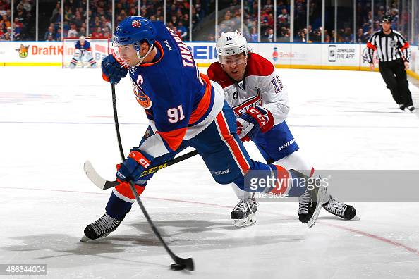 John Tavares of the New York Islanders takes a shot on goal under pressure from PA Parenteau of the Montreal Canadiens at Nassau Veterans Memorial...