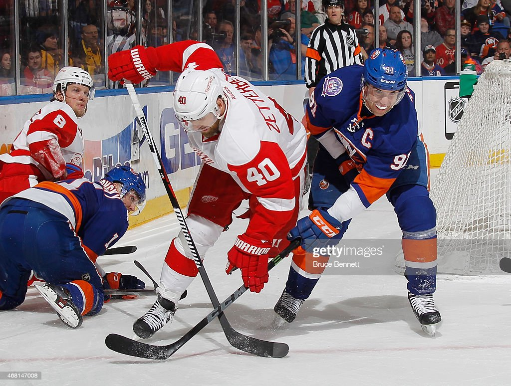 <a gi-track='captionPersonalityLinkClicked' href=/galleries/search?phrase=John+Tavares&family=editorial&specificpeople=601791 ng-click='$event.stopPropagation()'>John Tavares</a> #91 of the New York Islanders trips up <a gi-track='captionPersonalityLinkClicked' href=/galleries/search?phrase=Henrik+Zetterberg&family=editorial&specificpeople=201520 ng-click='$event.stopPropagation()'>Henrik Zetterberg</a> #40 of the Detroit Red Wings at the Nassau Veterans Memorial Coliseum on March 29, 2015 in Uniondale, New York. The Islanders defeated the Red Wings 5-4.