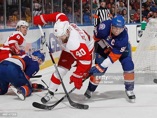 John Tavares of the New York Islanders trips up Henrik Zetterberg of the Detroit Red Wings at the Nassau Veterans Memorial Coliseum on March 29 2015...
