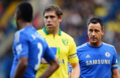 John Terry and Ashley Cole of Chelsea look on as they mark Grant Holt of Norwich City during the Barclays Premier League match between Chelsea and...