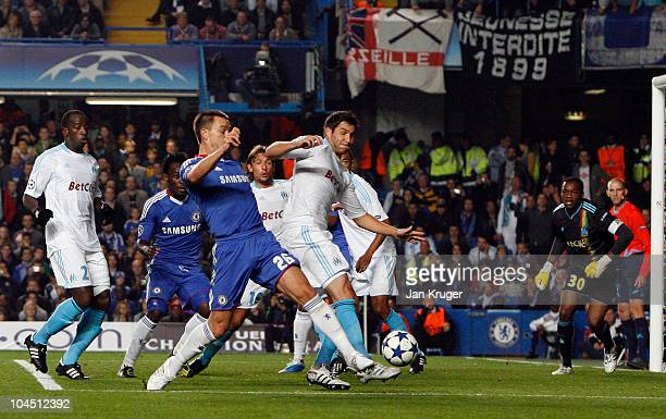 John Terry Captain of Chelsea beats AndrePierre Gignac to score his team's first goal during the UEFA Champions League Group F match between Chelsea...