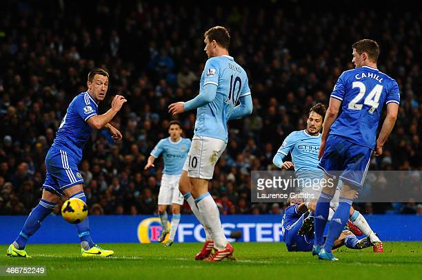 John Terry of Chelsea and Edin Dzeko of Manchester City watch the ball as David Silva of Manchester City's effort on goal goes wide during the...
