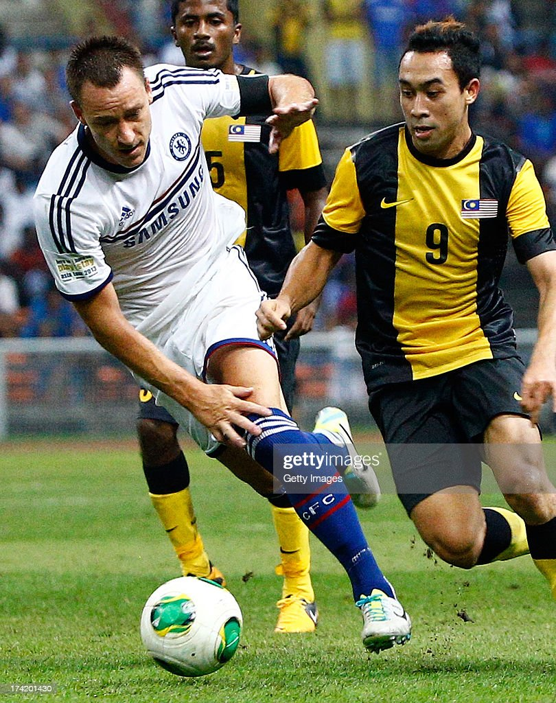 John Terry of Chelsea FC and Norsharul of Malaysia compete for the ball during the match between Chelsea and Malaysia XI on July 21, 2013 at the Shah Alam Stadium, Kuala Lumpur, Malaysia.