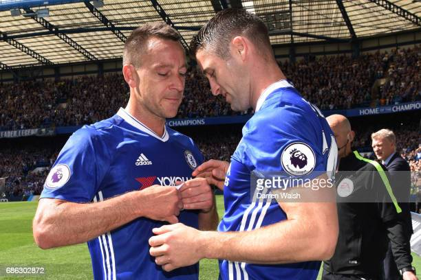 John Terry of Chelsea hands the captains arm band to Gary Cahill of Chelsea as he is subbed off during the Premier League match between Chelsea and...