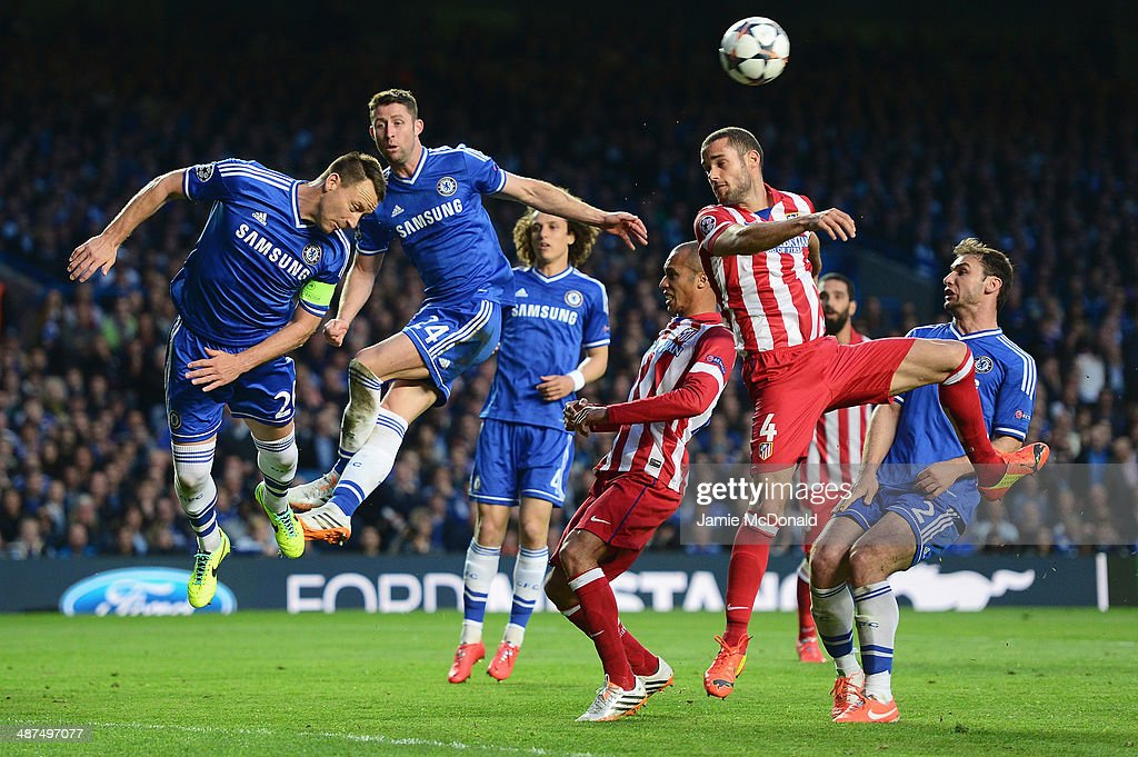 John Terry of Chelsea heads clear as he is closed down by Mario Suarez of Club Atletico de Madrid during the UEFA Champions League semi-final second leg match between Chelsea and Club Atletico de Madrid at Stamford Bridge on April 30, 2014 in London, England.