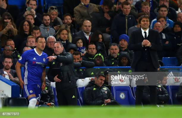 John Terry of Chelsea is given instructions by assistant manager Steve Holland as Antonio Conte manager of Chelsea looks on during the Premier League...