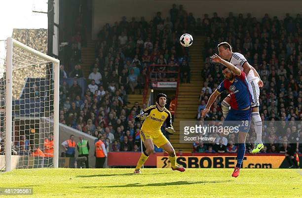 John Terry of Chelsea is pressurised by Joe Ledley of Crystal Palace and heads the ball over his goalkeeperPetr Cech to open the scoring with an own...