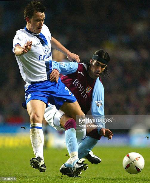 John Terry of Chelsea is tackled by Juan Pablo Angel of Aston Villa during the Carling Cup Quarter Final match between Aston Villa and Chelsea at...