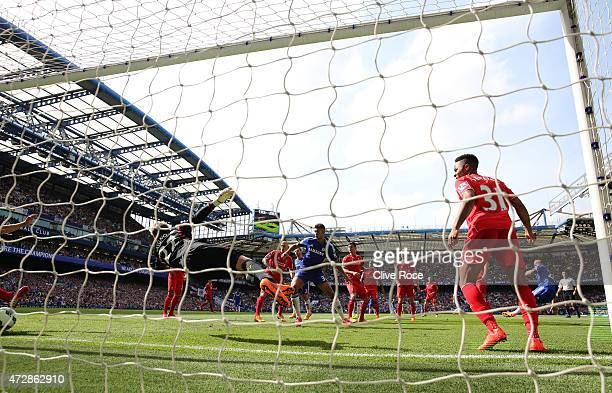 John Terry of Chelsea scores the opening goal past the diving goalkeeper Simon Mignolet of Liverpool during the Barclays Premier League match between...