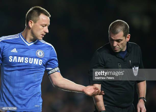 John Terry of Chelsea shows referee Phil Dowd a coin thrown from the crowd during the Barclays Premier League match between Chelsea and Manchester...