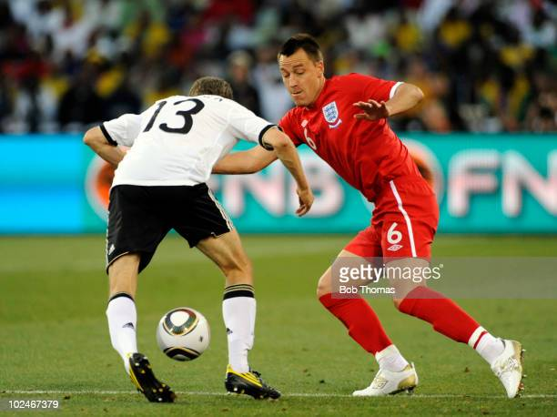 John Terry of England fights for a loose ball with Thomas Mueller of Germany during the 2010 FIFA World Cup South Africa Round of Sixteen match...