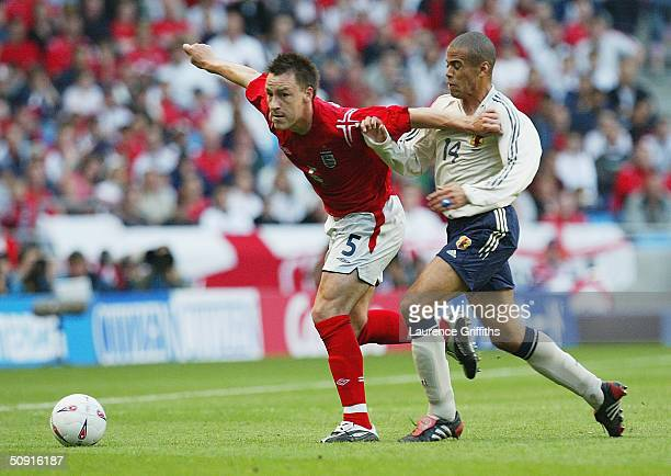 John Terry of England holds back Alessandro Santos of Japan during the match between England and Japan held at the City of Manchester Stadium on June...