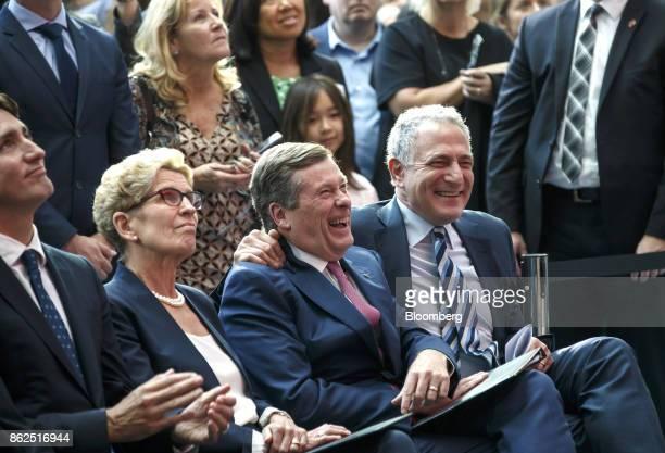 John Tory mayor of Toronto center and Dan Doctoroff chief executive officer of Sidewalk Labs LLC right smile as Kathleen Wynne premier of Ontario...