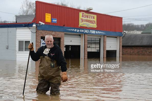 John Tosti owner of Tosti's Transmission wades in the water after inspecting his business as it takes on floodwater on December 30 2015 in Fenton...