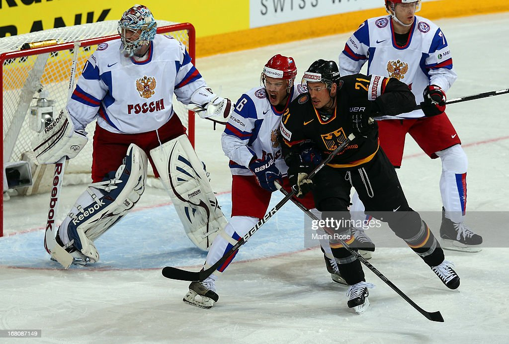 John Tripp (R) of Germany and Denis Denisov (#6) of Russia battle for position during the IIHF World Championship group H match between Germany and Russia at Hartwall Areena on May 5, 2013 in Helsinki, Finland.