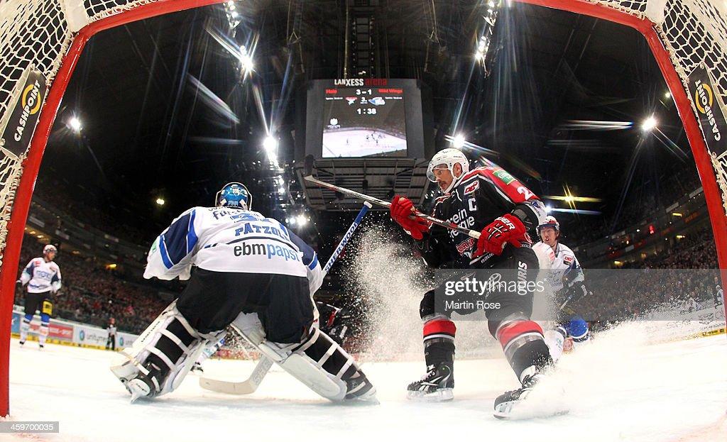 John Tripp of Koeln fails to score over Dimitri Paetzold goaltender of Schwenningen during the DEL match between Koelner Haie and Schwenninger Wild...