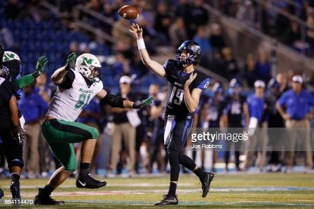 John Urzua of the Middle Tennessee Blue Raiders looks to pass while under pressure from Ryan Bee of the Marshall Thundering Herd in the third quarter...