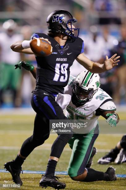 John Urzua of the Middle Tennessee Blue Raiders looks to pass while under pressure from Frankie Hernandez of the Marshall Thundering Herd in the...