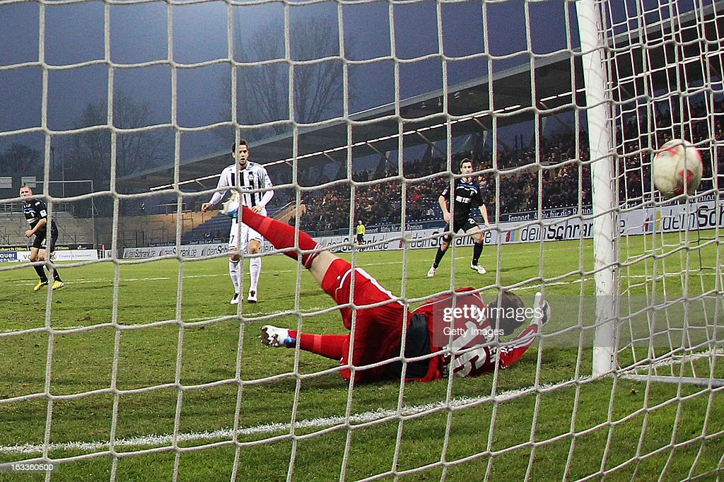 John Verhoek (L) of Frankfurt scores his team's first goal against goalkeeper Jasmin Fejzic of Aalen (R) during the Second Bundesliga match between FSV Frankfurt and VfR Aalen at Frankfurter Volksbank Stadium on March 8, 2013 in Frankfurt am Main, Germany.