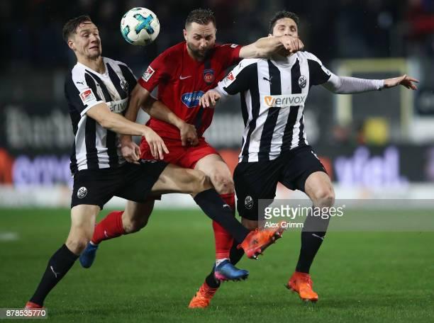 John Verhoek of Heidenheim is challenged by Tim Knipping and Tim Kister of Sandhausenduring the Second Bundesliga match between SV Sandhausen and 1...