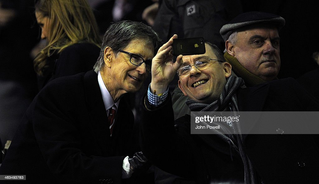 John W Henry owner of Liverpool poses for a picture with a fan before the Barclays Premier League Match between Liverpool and Aston Villa at Anfield on January 18, 2014 in Liverpool, England.