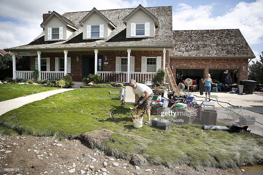 John Waida of Longmont, Colorado and his future daughter-in-law Tyra Thorstad of Seattle, Washington work to remove flood damaged items as residents clean up in the wake of a week of heavy flooding on September 16, 2013 in Longmont, Colorado. More than 600 people are unaccounted for and thousands were forced to evacuate after historic flooding devastated communities in Colorado.